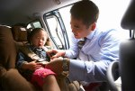 getty_rm_photo_of_father_buckling_daughter_into_car_seat